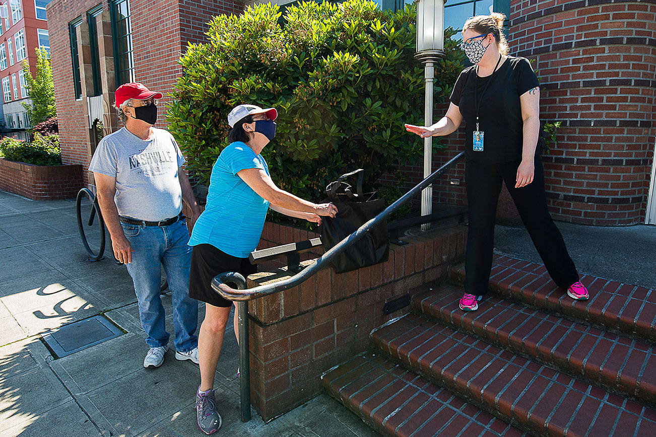 Leslie Bringedahl grabs a bag containing books she and her husband Mark ordered after Circulation Manager Carol  puts them down on a wall during curbside pickup at the Everett Public Library on Wednesday, June 17, 2020 in Everett, Wa.(Andy Bronson / The Herald)