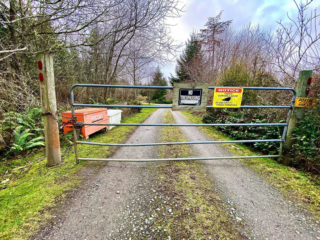 A gate blocks the entrance to the $6 million survival compound in Coupeville on 60 acres. (Andrea Brown / The Herald)