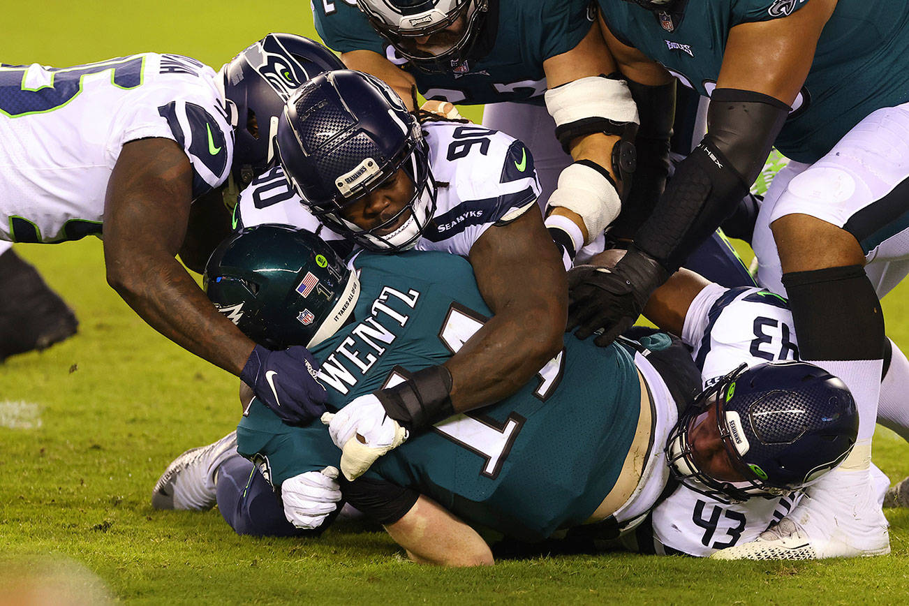 Philadelphia Eagles quarterback Carson Wentz (11) is sacked by Benson Mayowa (95), Jarran Reed (90) and Carlos Dunlap (43) during the first half of an NFL football game, Monday, Nov. 30, 2020, in Philadelphia. The Seahawks defeated the Eagles (AP Photo/Rich Schultz)