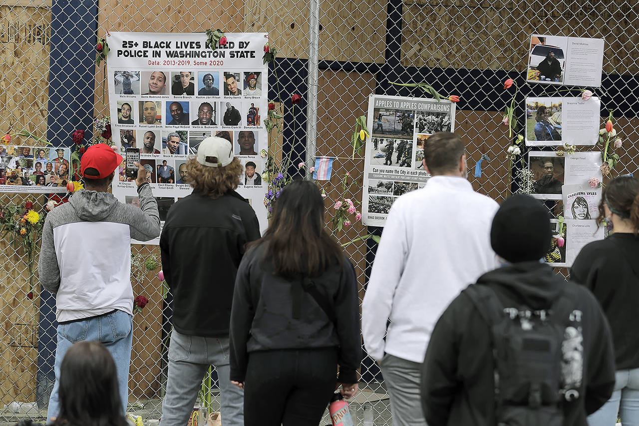 Visitors view photos of people who were killed by police in Washington State and elsewhere, June 16, inside what was called the Capitol Hill Occupied Protest zone in Seattle. (AP Photo/Ted S. Warren, file)