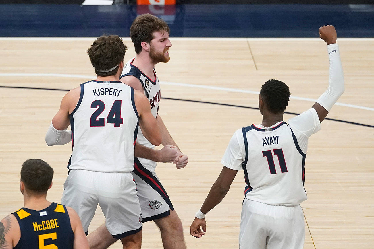 Gonzaga's Drew Timme (2) celebrates with Corey Kispert (24) and Joel Ayayi (11) after Timme made a shot and was fouled during the second half of the team's NCAA college basketball game against West Virginia, Wednesday, Dec. 2, 2020, in Indianapolis. (AP Photo/Darron Cummings)
