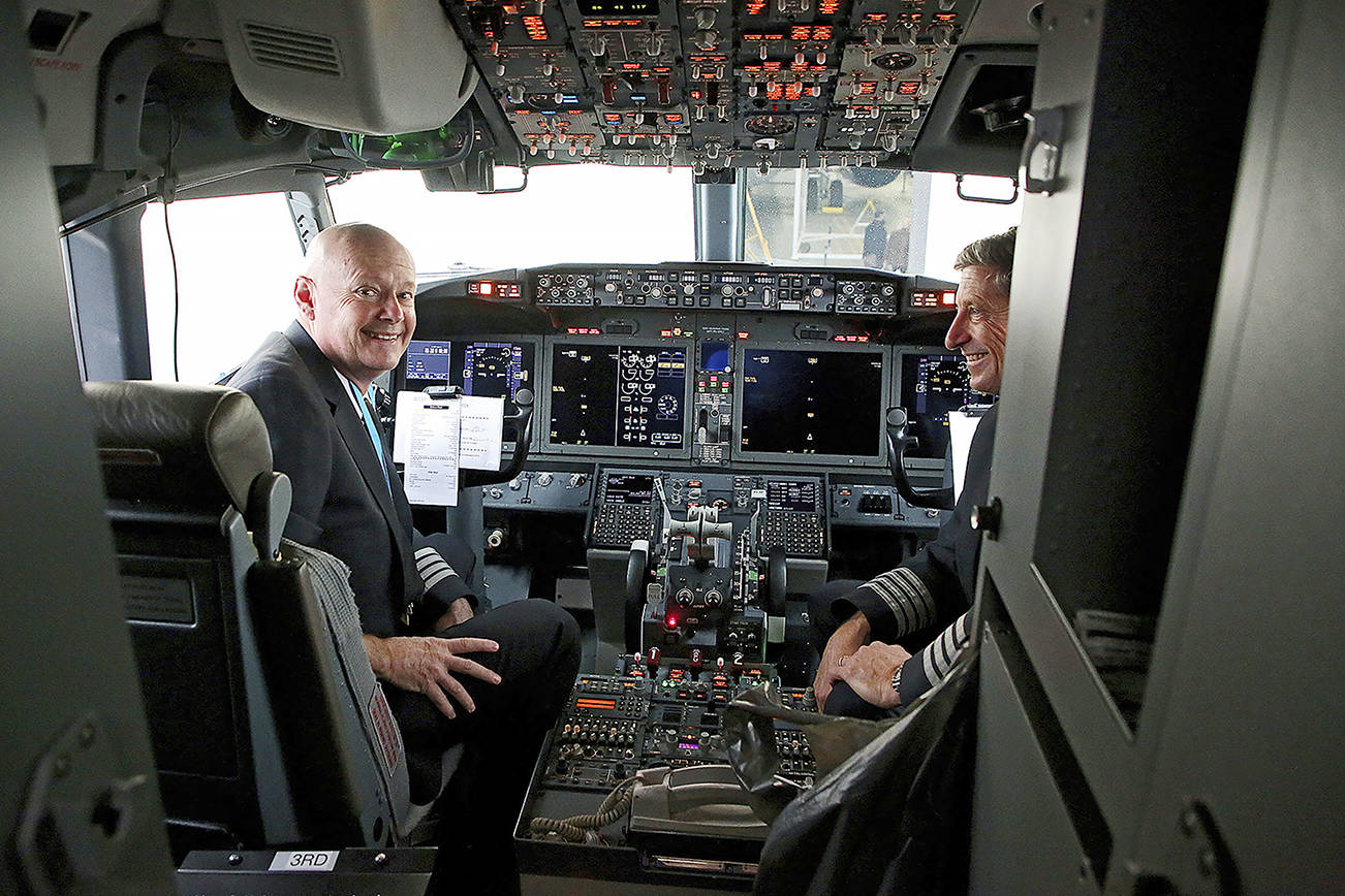 Pilots Peter Gamble, left, and John Konstanzer talk with journalists and crew members after flying a Boeing 737 Max from Dallas and arriving at the American Airlines Tulsa maintenance facility Wednesday, Dec. 2, 2020 in Tulsa, Okla.. Earlier the plane had flown a group of journalists and American Airlines employees from Dallas to the American Airlines Tulsa maintenance facility. (Mike Simons/Tulsa World via AP)