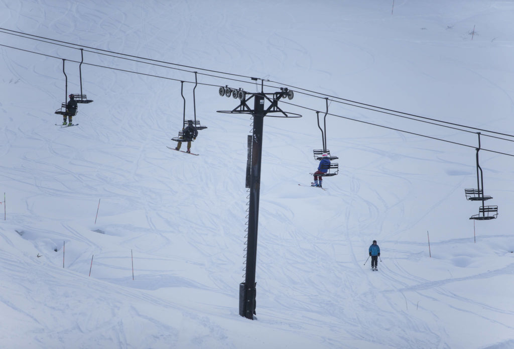 People ride one person to a chair on opening day at Stevens Pass last Friday. (Olivia Vanni / The Herald)
