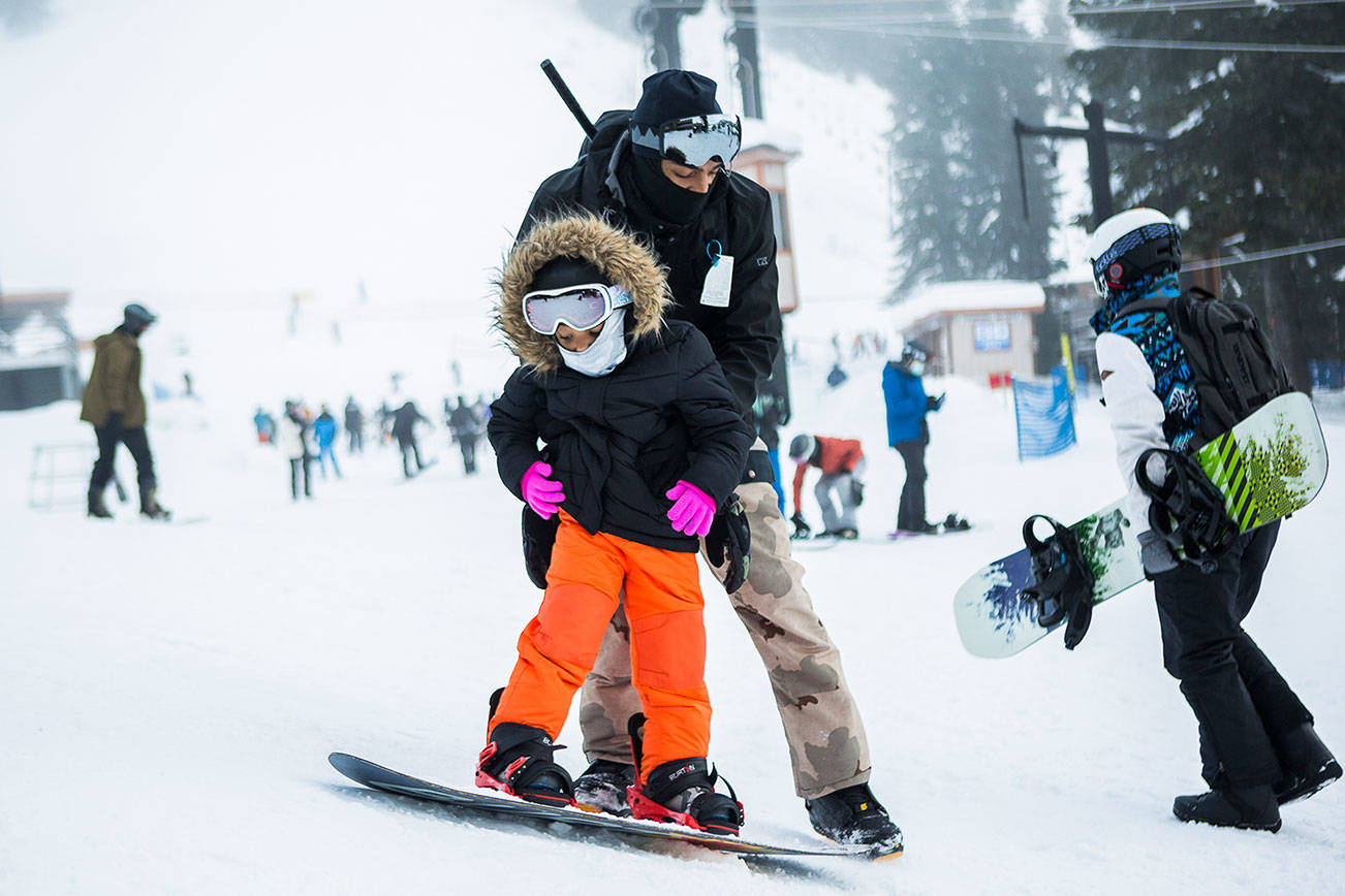 Jarrell Banks helps his daughter Londyn, 4, learn how to stop on her snowboard during her first time snowboarding on opening day at Steven's Pass on Friday, Dec. 4, 2020. (Olivia Vanni / The Herald)