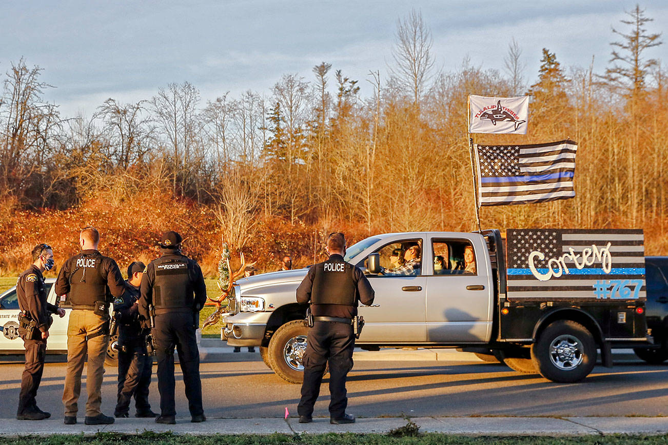 Law enforcement officers watch the procession of the memorial parade for fallen and missing Tulalip officer Charlie Cortez Saturday afternoon on the Tulalip Reservation on December 12, 2020.  (Kevin Clark / The Herald)