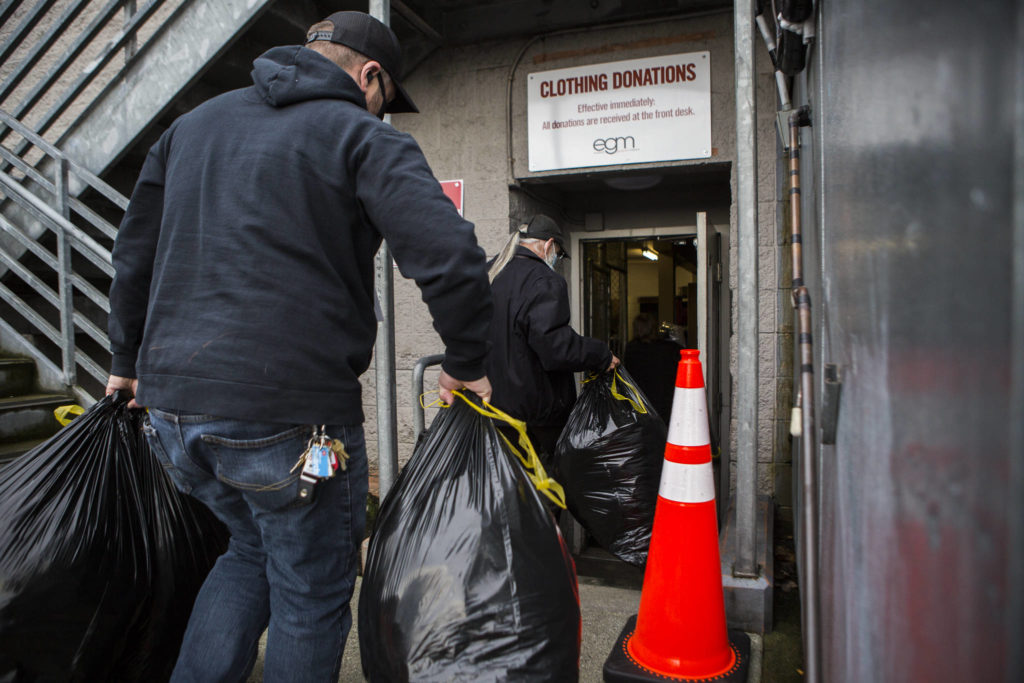 Bags filled with coats and other donations from Tonja Jones are carried inside the Everett Gospel Mission on Dec. 10. (Olivia Vanni / The Herald)