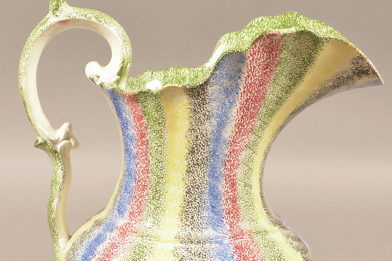 This 11-inch-high antique rainbow spatterware water picture with bands in five different colors sold for more than $5,000 at a Conestoga auction this year. Notice the double G-scroll handle, an added value feature. (Cowles Syndicate Inc.)