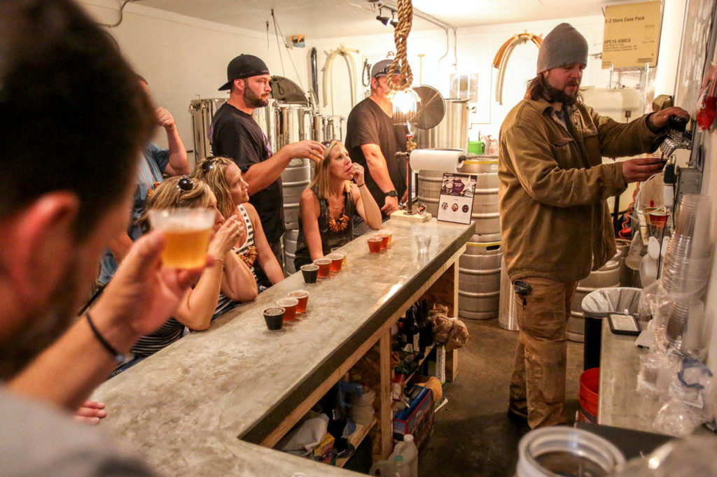 Greg Krsak, owner and operator of Scrappy Punk Brewery, pours samples during the 2017 Snoho Brew Tour. (Kevin Clark / The Herald)