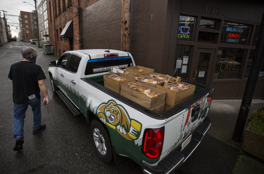 Jim Staniford loads up his truck bed with meals to be delivered Thursday to the Everett Gospel Mission in Everett. (Olivia Vanni / The Herald)