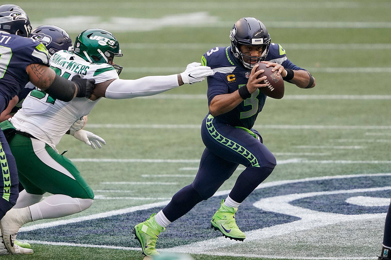 Seattle Seahawks quarterback Russell Wilson, right, scrambles against the New York Jets during the first half of an NFL football game, Sunday, Dec. 13, 2020, in Seattle. (AP Photo/Ted S. Warren)