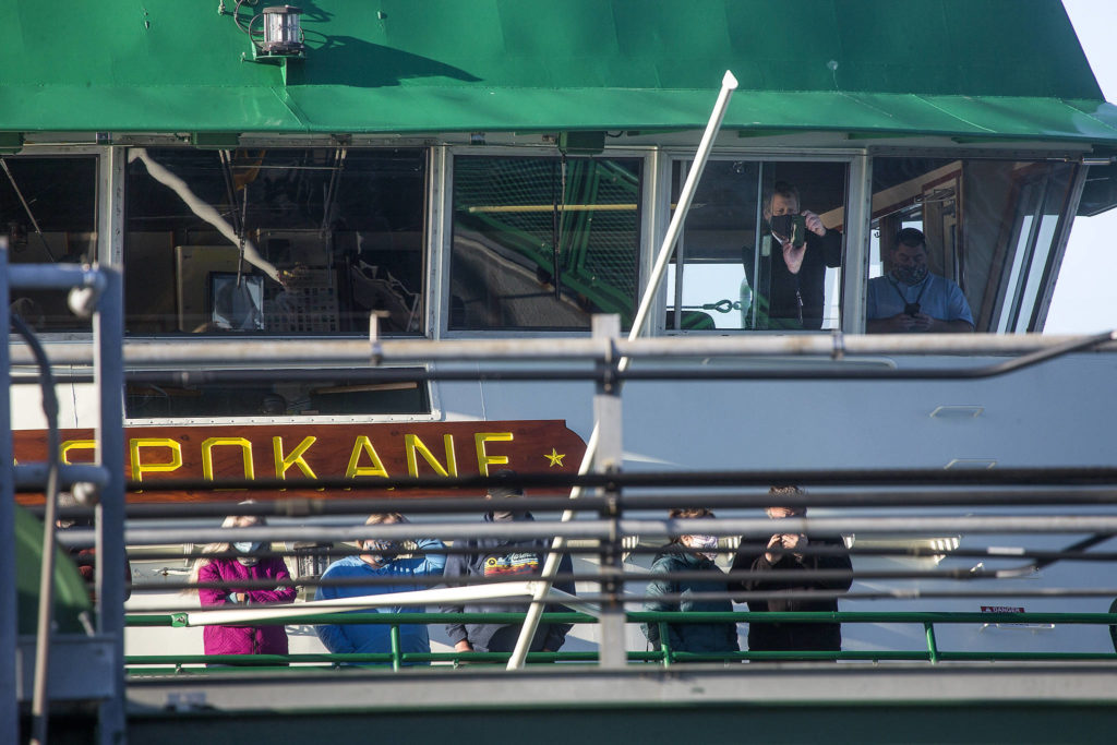 From the bridge of the MV Spokane, a Washington State Ferries crew takes photos of spilled logs blocking the ramp of the Edmonds terminal on Monday. (Andy Bronson / The Herald)