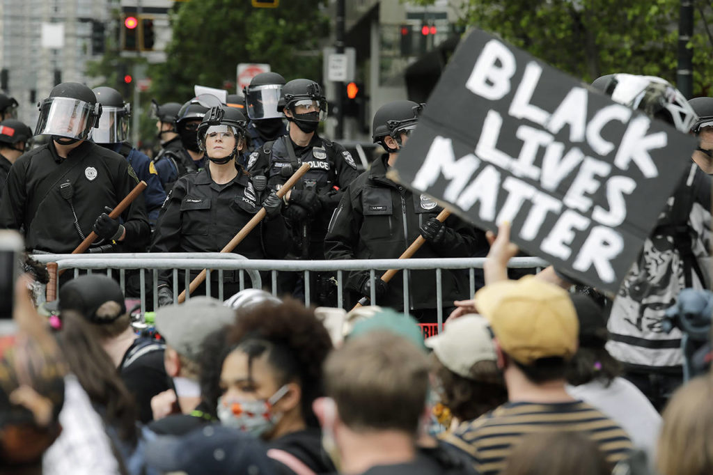 In this June 3 photo, police officers behind a barricade look on as protesters fill the street in front of Seattle City Hall in Seattle, following protests over the death of George Floyd, a Black man who was in police custody in Minneapolis. Protests in Seattle over the killing of Floyd were among Washington state's top stories for 2020. (AP Photo/Elaine Thompson, File)