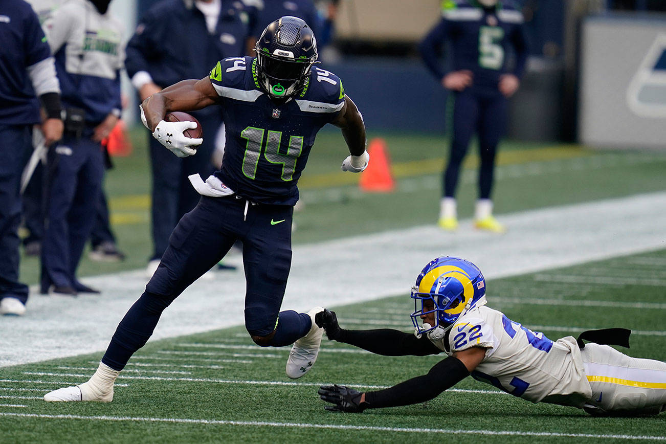 Seattle Seahawks wide receiver DK Metcalf (14) in action against Los Angeles Rams cornerback Troy Hill (22) during the first half of an NFL football game, Sunday, Dec. 27, 2020, in Seattle. (AP Photo/Elaine Thompson)