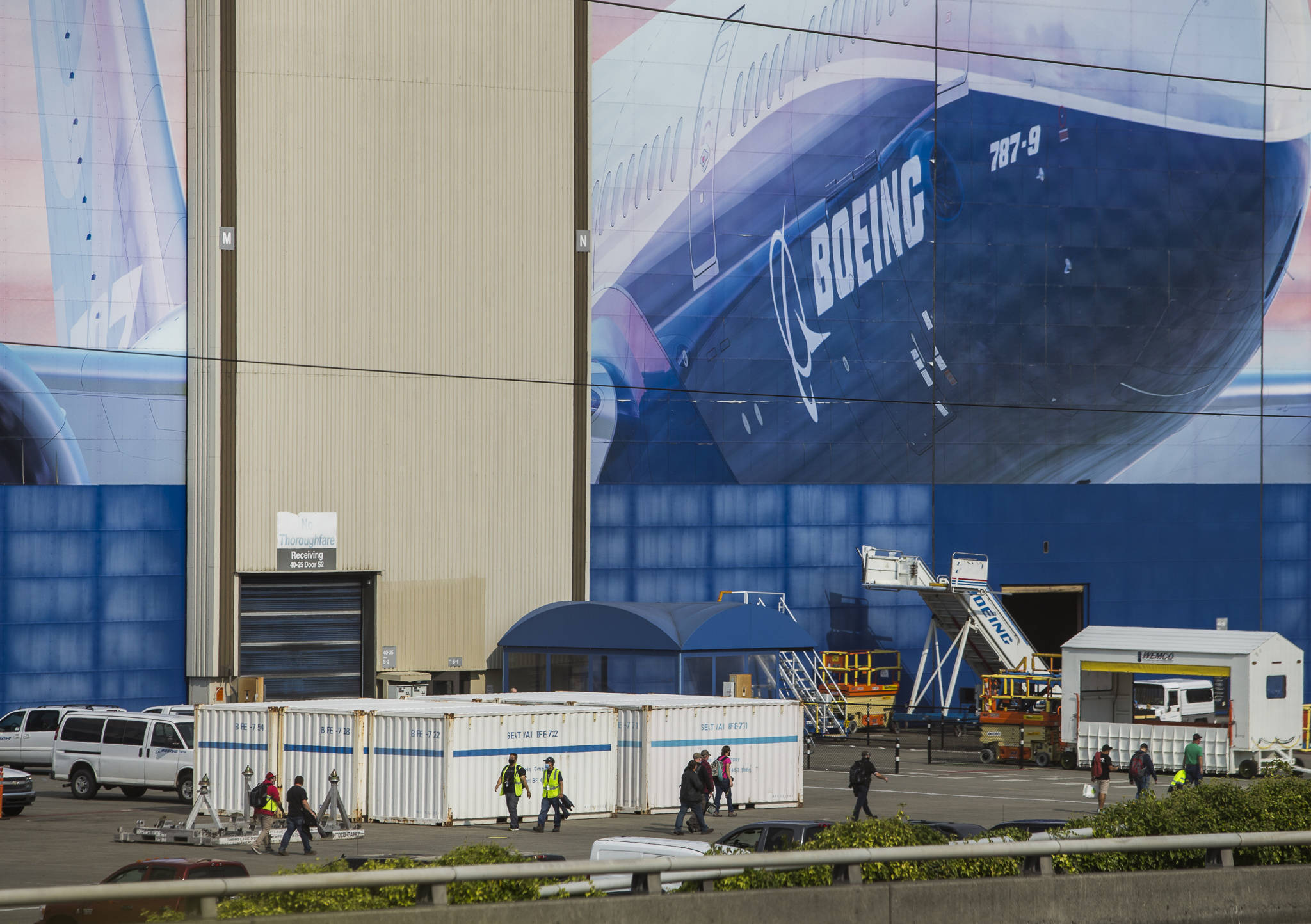 Boeing workers walk to and from their cars during a shift change on Oct. 1 in Everett. (Olivia Vanni / The Herald)
