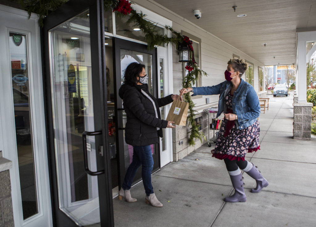 Snohomish Delivers concierge Sarah Dylan Jensen hands off a delivery to Snohomish Senior Center executive director Sharon Burlison on Tuesday in Snohomish. (Olivia Vanni / The Herald)