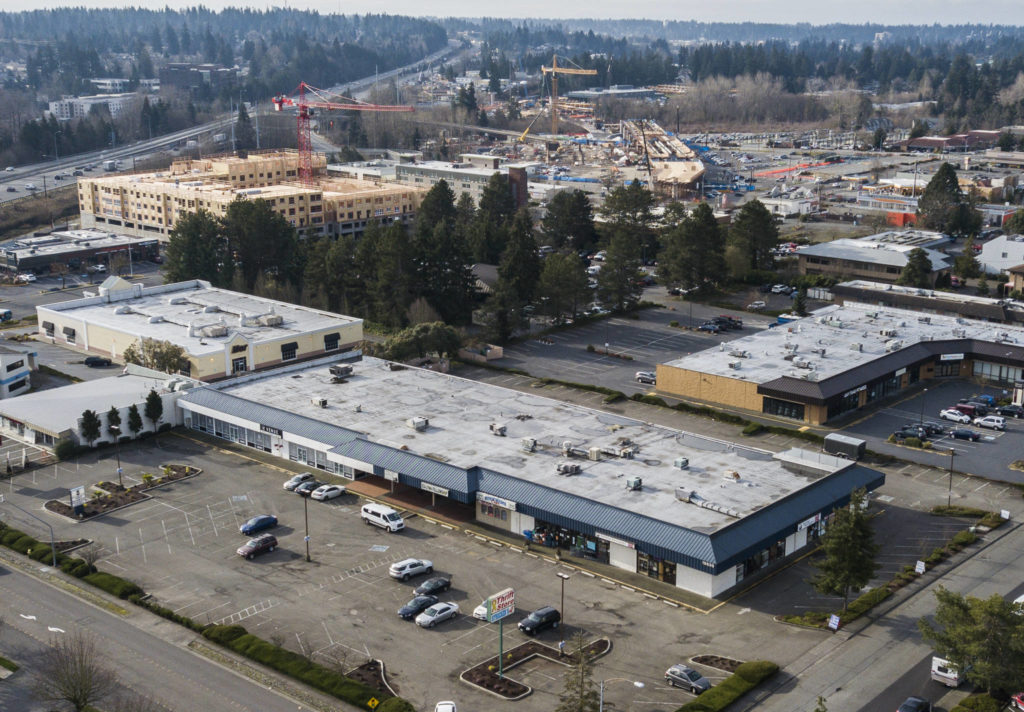 The Lynnwood strip-mall site (bottom) where Trent Development hopes to build 350 studio, one-bedroom and two-bedroom apartments. In the background is the Sound Transit Link light rail station that is under construction. (Olivia Vanni / The Herald)