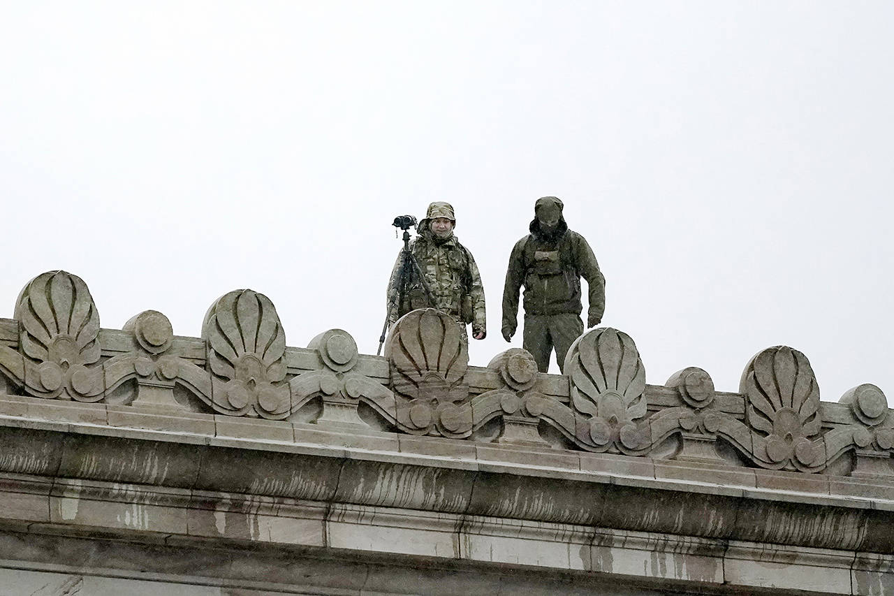 Law enforcement officers stand atop the Capitol in anticipation of protests Monday at the Capitol in Olympia. (AP Photo/Ted S. Warren)