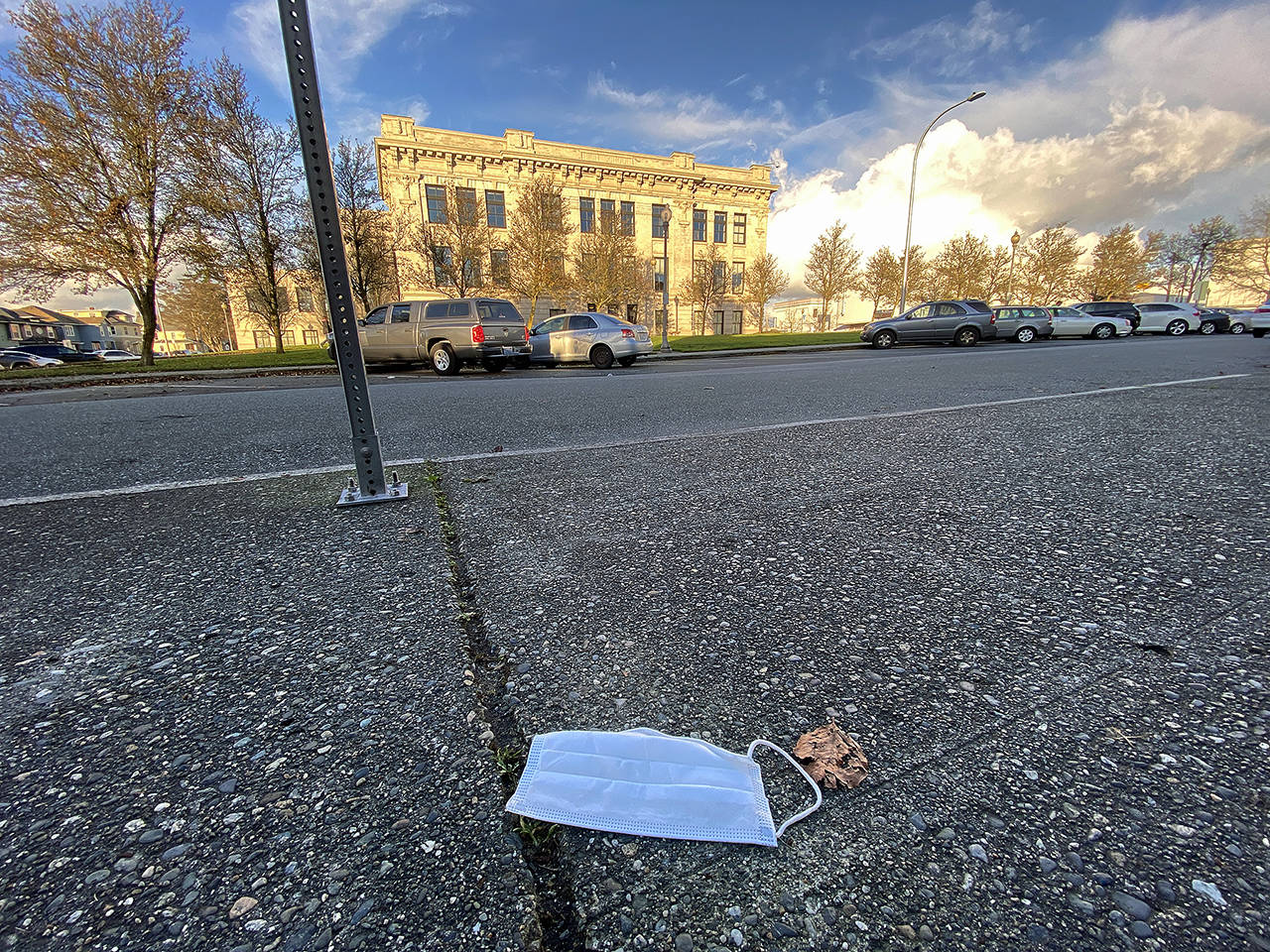 A discarded face mask lies on the sidewalk across the street from Everett High School last December. (Sue Misao / The Herald)