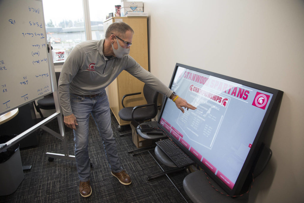 Athletic Director Tom Wilfong demonstrates a touchscreen display that will replace many of the plaques and photos that list school academic and sports records. (Andy Bronson / The Herald)