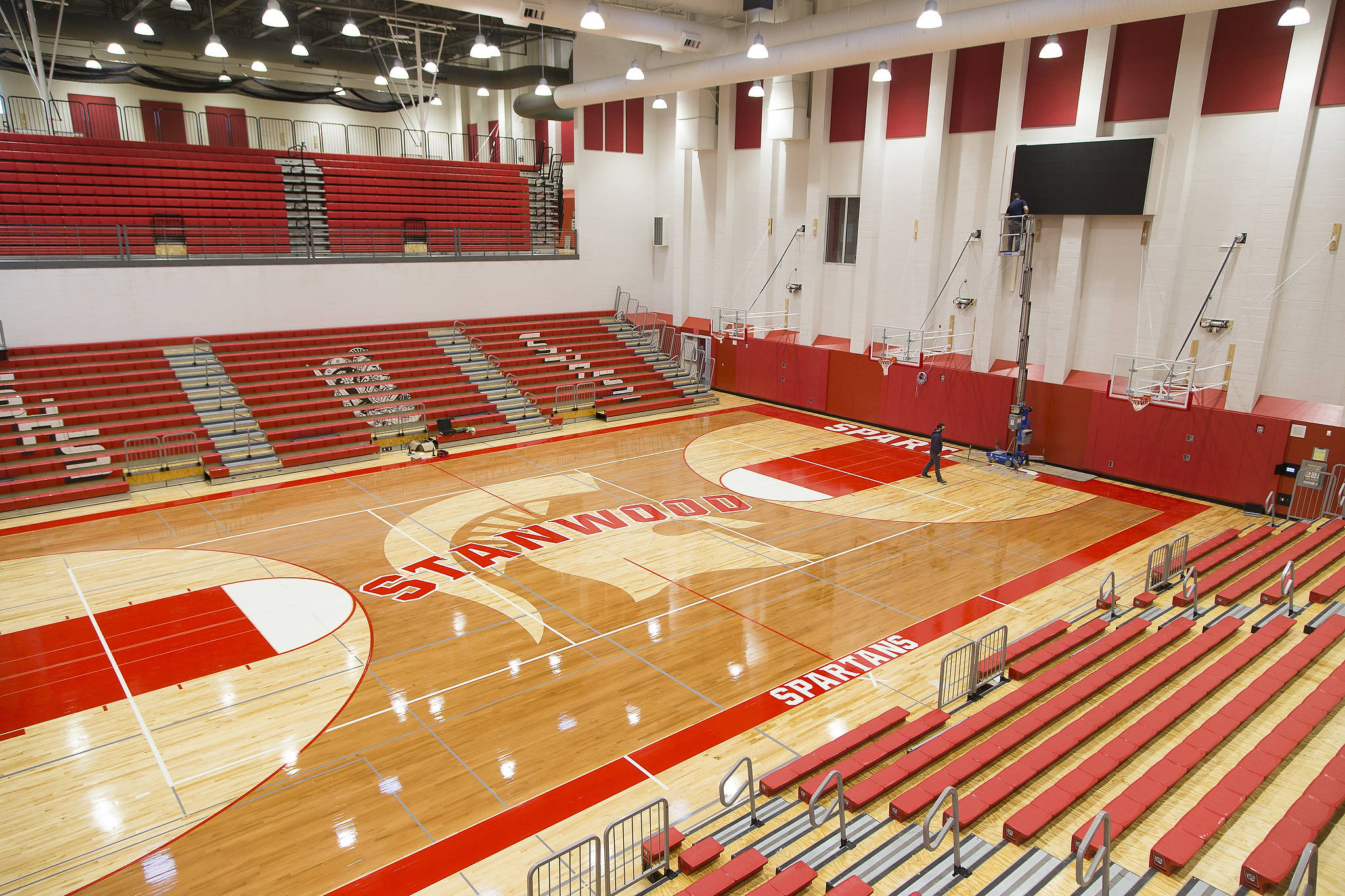 Crews work on the video display Wednesday in the main gym at Stanwood High School. (Andy Bronson / The Herald)