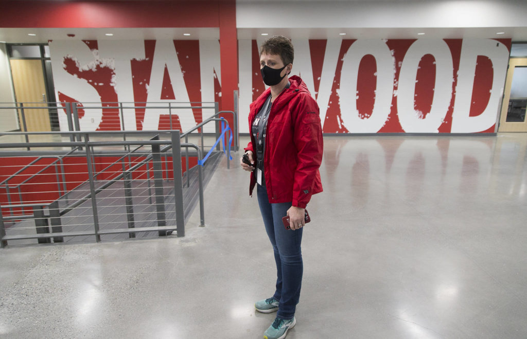 Stanwood High School Principal Christine Del Pozo stands in the main hallway Wednesday where a Stanwood sign awaits touch-up paint. (Andy Bronson / The Herald)