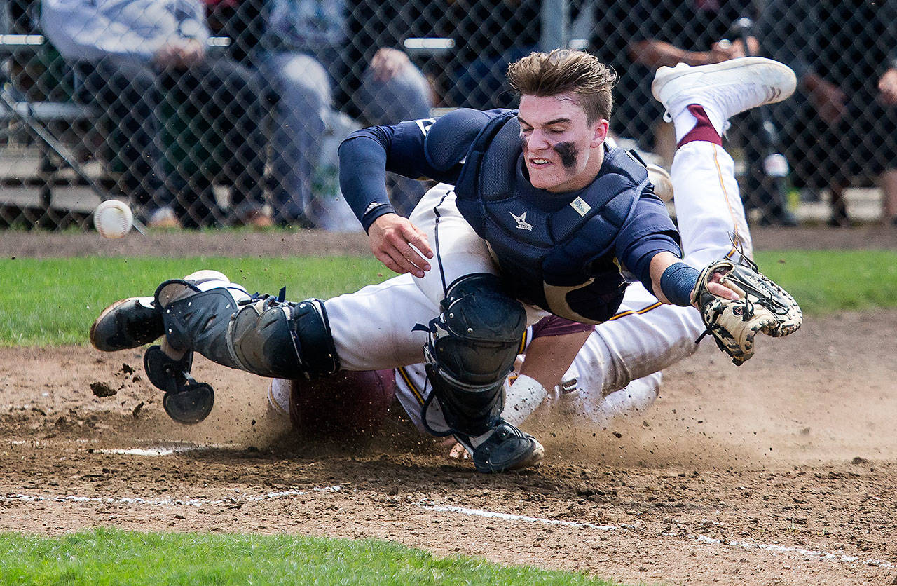 Arlington's Jack Sheward (front) reaches for the ball as O'Dea's David Sessoms slides into home during a 3A baseball state regional game on May 18, 2019, at Sherman Anderson Field in Mount Vernon. (Andy Bronson / The Herald)