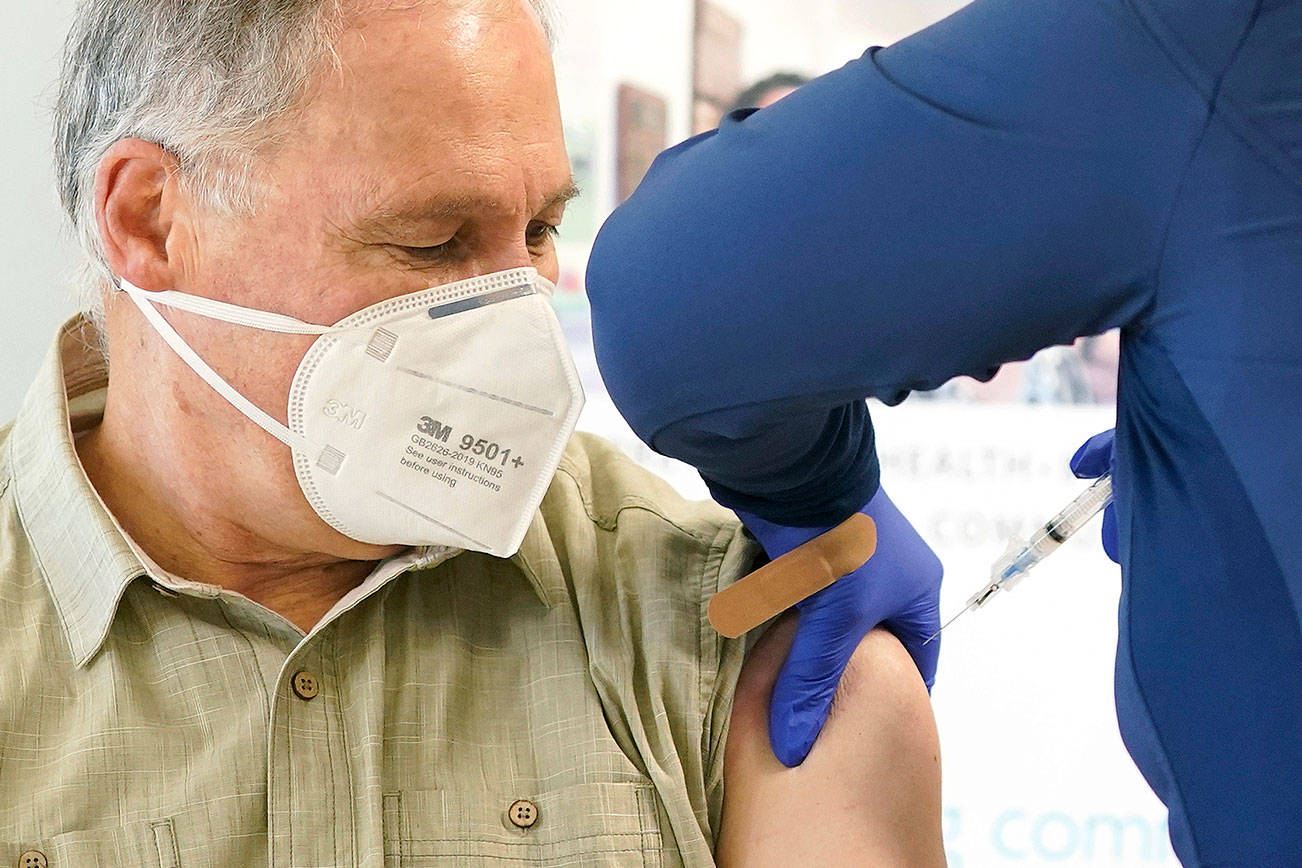 Washington Gov. Jay Inslee, left, gets the first shot of the Moderna COVID-19 vaccine, Friday, Jan. 22, 2021, from Elizabeth Smalley, right, a medical assistant at a Sea Mar Community Health Center in Olympia, Wash. Inslee's wife Trudi also received the first dose of the vaccine. (AP Photo/Ted S. Warren)