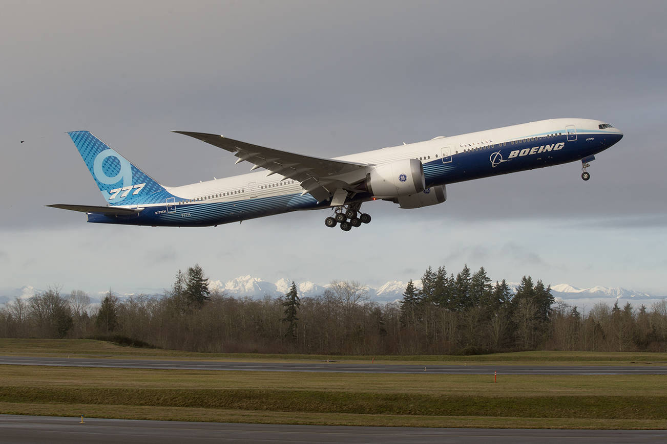 With the Olympic mountains in the background, Boeing's 777X lifts off from Paine Field on its first flight, to Boeing Field in Seattle, on Saturday, Jan. 25, 2020 in Everett, Wash. (Andy Bronson / The Herald)