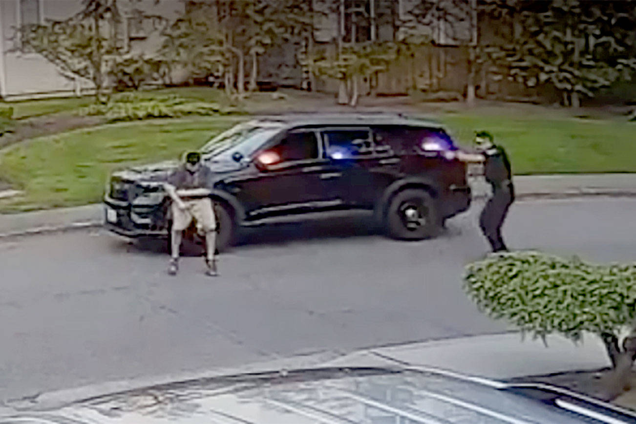 A frame from video taken by a nearby security camera shows a Bothell police officer (right) shooting a man who allegedly charged him with a knife. (Snohomish County Multiple Agency Response Team) 20210128