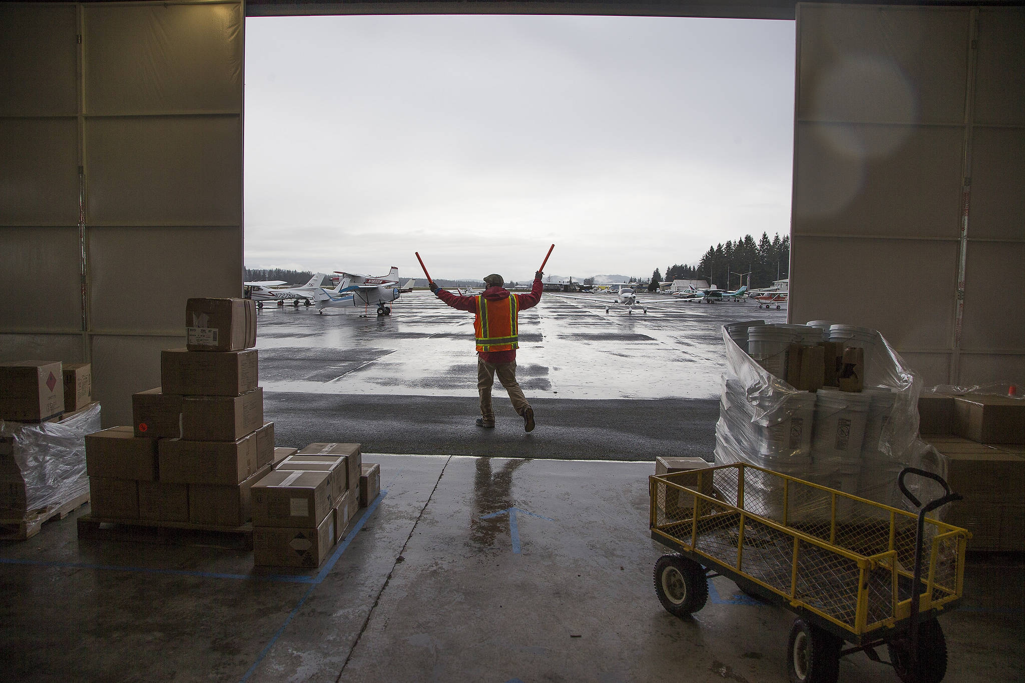 A volunteer directs a plane to a spot where it can be loaded with PPE supplies for an airlift to Native American tribes in Washington. (Andy Bronson / The Herald)