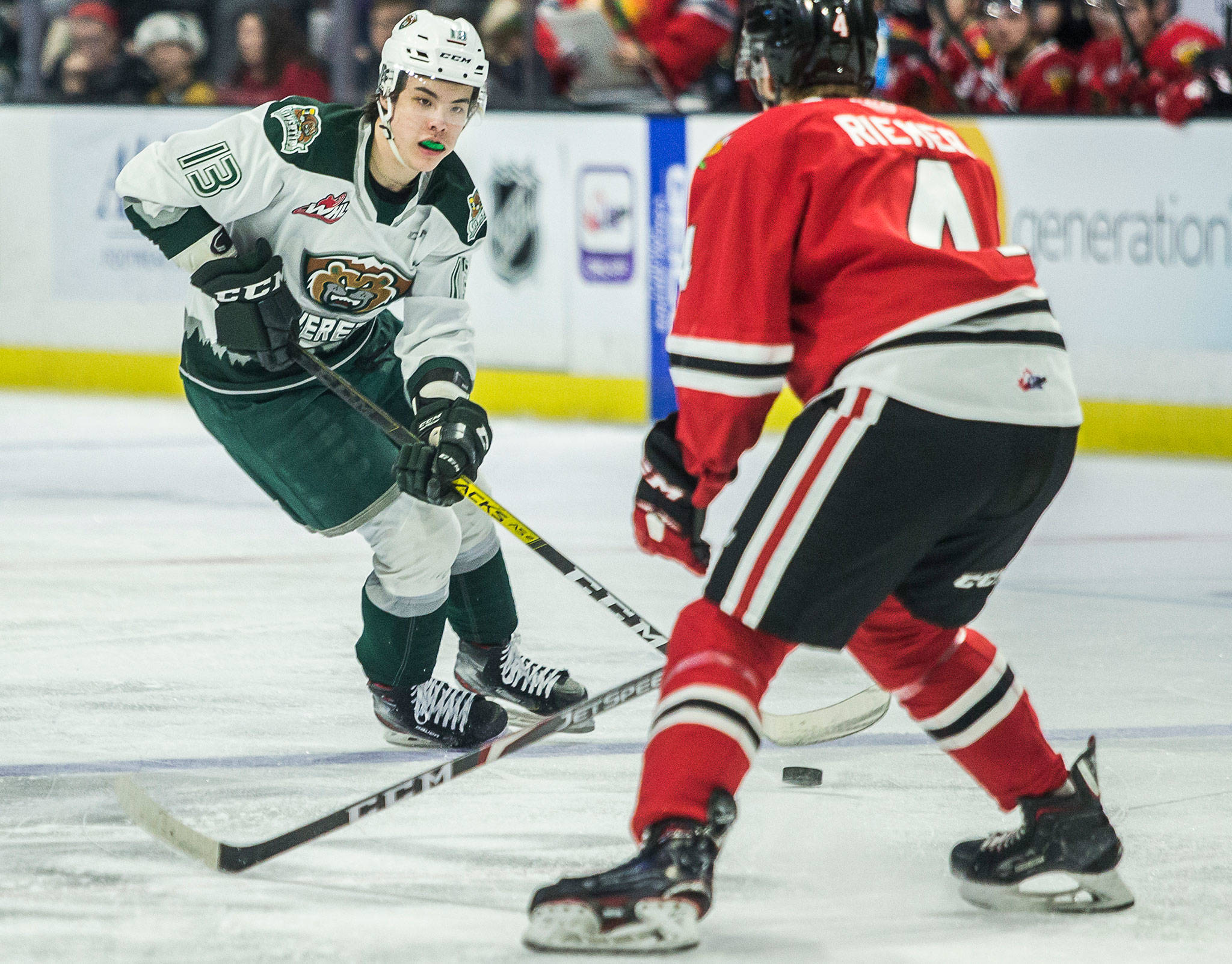 The Silvertips' Brendan Lee (left) skates with the puck during a game against the Winterhawks on March 1, 2020, in Everett. (Olivia Vanni / The Herald)