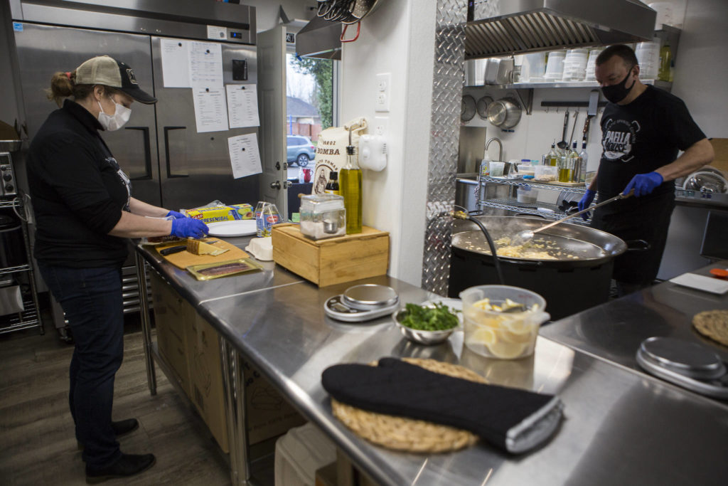 Laura and Greg McLaughlin work on to-go orders in the kitchen they built in their garage. (Olivia Vanni / The Herald)