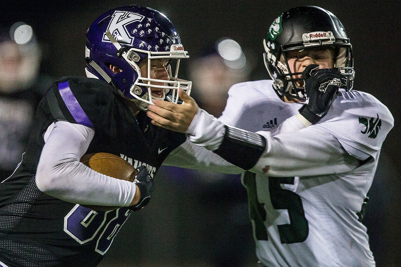 Kamiak's Ben Farrara and Jackson's Jack Barclay grab each others facemasks during the game on Nov. 1, 2019 in Everett, Wash. (Olivia Vanni / The Herald)