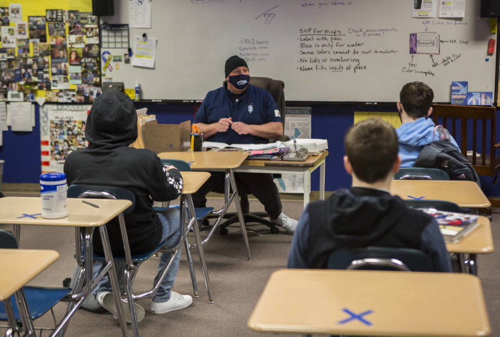 Students sit social distanced, with sanitizing wipes within reach, during a social sciences class on Thursday in Sultan. (Olivia Vanni / The Herald)