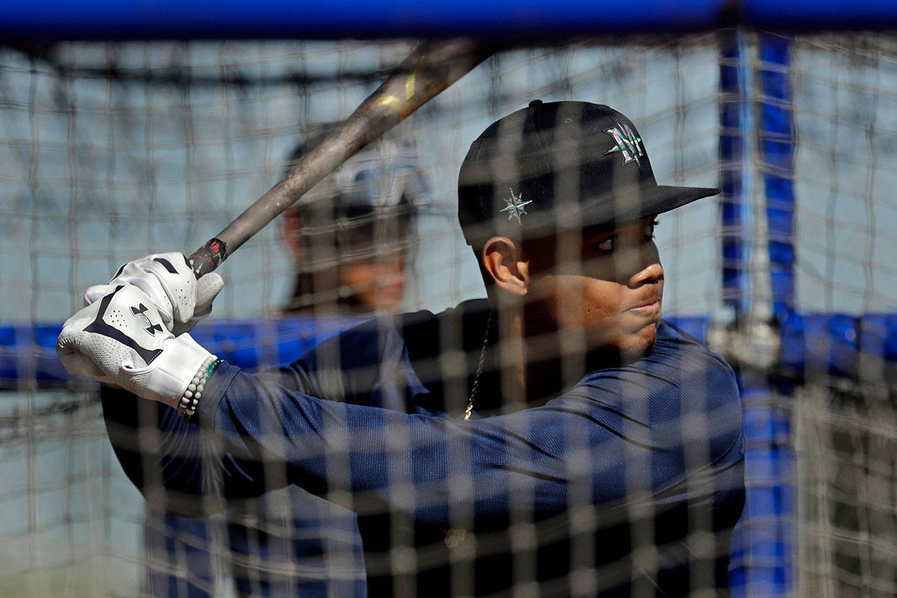 Seattle Mariners' Julio Rodriguez bats during spring training baseball practice Thursday, Feb. 13, 2020, in Peoria, Ariz. (AP Photo/Charlie Riedel)