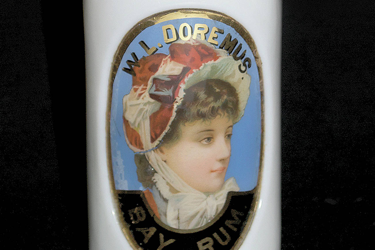 Silly as it may seem, milk glass can be one of many colors. It is an opaque glass first used in the 1800s and now prized in collections of barber bottles of the Victorian era. This 10½-inch-high milk glass barber bottle with a colorful label under glass sold for $200. (Cowles Syndicate Inc.)
