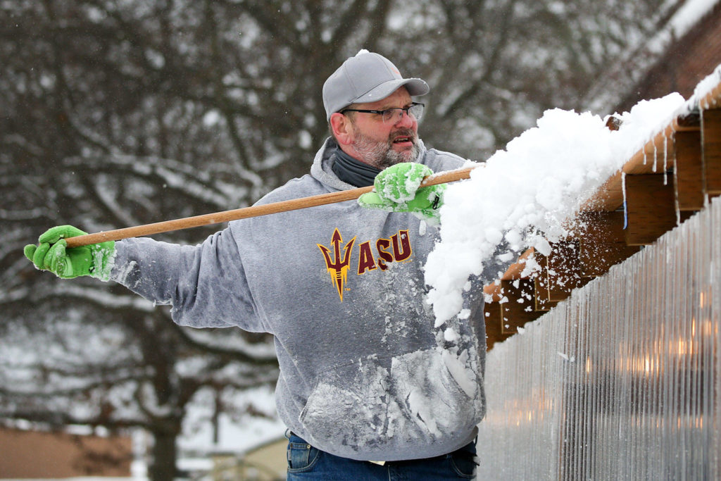 Jay Froehlich clears snow off the outdoor dinning space of Engle's Pub Saturday afternoon in Edmonds. (Kevin Clark / The Herald)