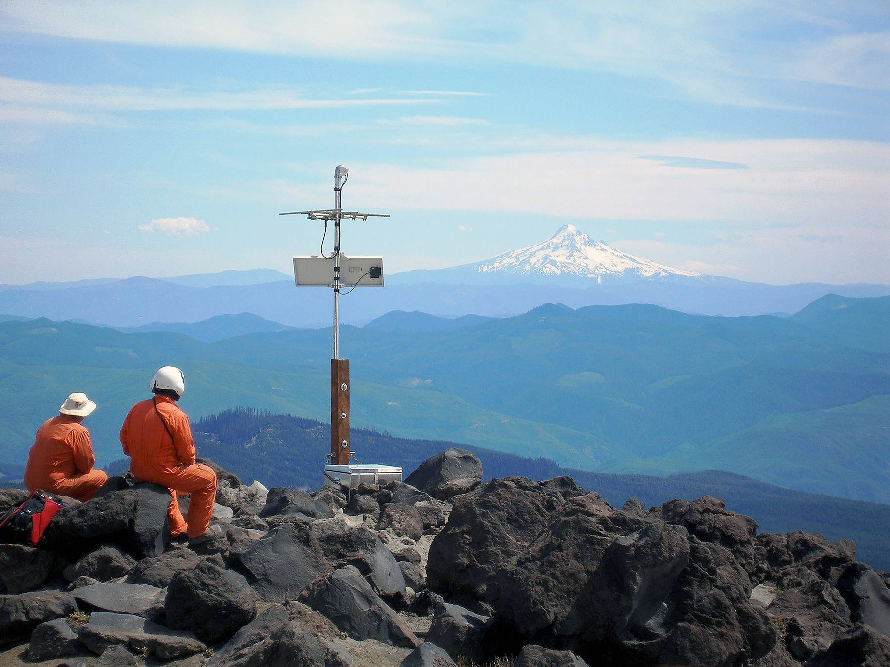 Karl Hagel and Pat McChesney, field engineers with the Pacific Northwest Seismic Network team at the University of Washington, install earthquake monitoring equipment on the slopes of Mount St. Helens, with Mount Hood in the distance. (Marc Biundo / University of Washington)