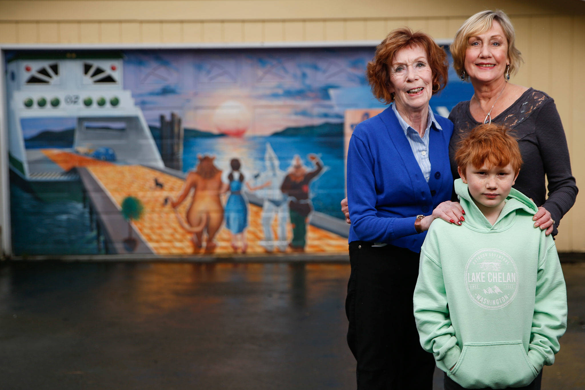 Sharon Pittman, her daughter Diana Jessen and her grandson Xander Pittman, 8, stand in front of a mural on the garage door of her home. It was painted in 2009 by Monroe muralist David Hose in 2009, who has done numerous murals around Snohomish County. (Kevin Clark / The Herald)