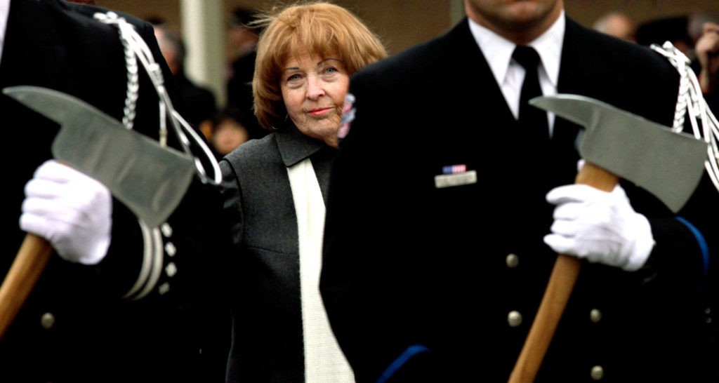 Kathy Parks, wife of slain firefighter Gary Parks, walks in a processional to place a flower on the memorial for her husband on the Everett Community College campus in 2012. (Michael O'Leary / Herald file)