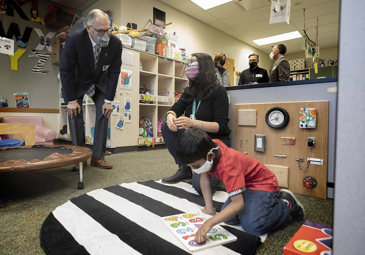 Washington State Governor Jay Inslee speaks with special ed Pre-K teacher Michelle Ling in her classroom at Phantom Lake Elementary School in Bellevue on Tuesday. (Ellen M. Banner/The Seattle Times via AP, Pool)