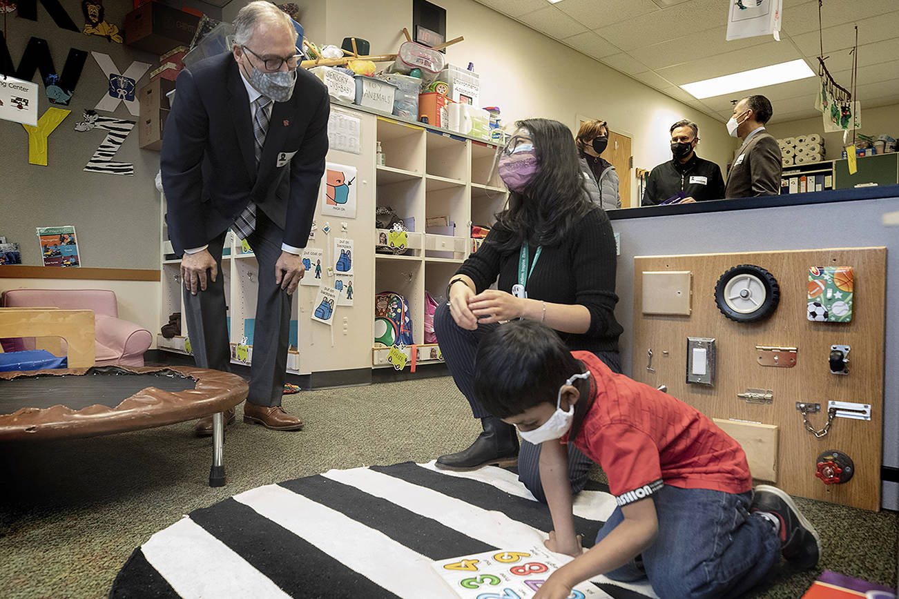 Washington State Governor Jay Inslee speaks with special ed Pre-K teacher Michelle Ling in her classroom at Phantom Lake Elementary School in Bellevue, Wash. Tuesday, March 2, 2021. (Ellen M. Banner/The Seattle Times via AP, Pool)