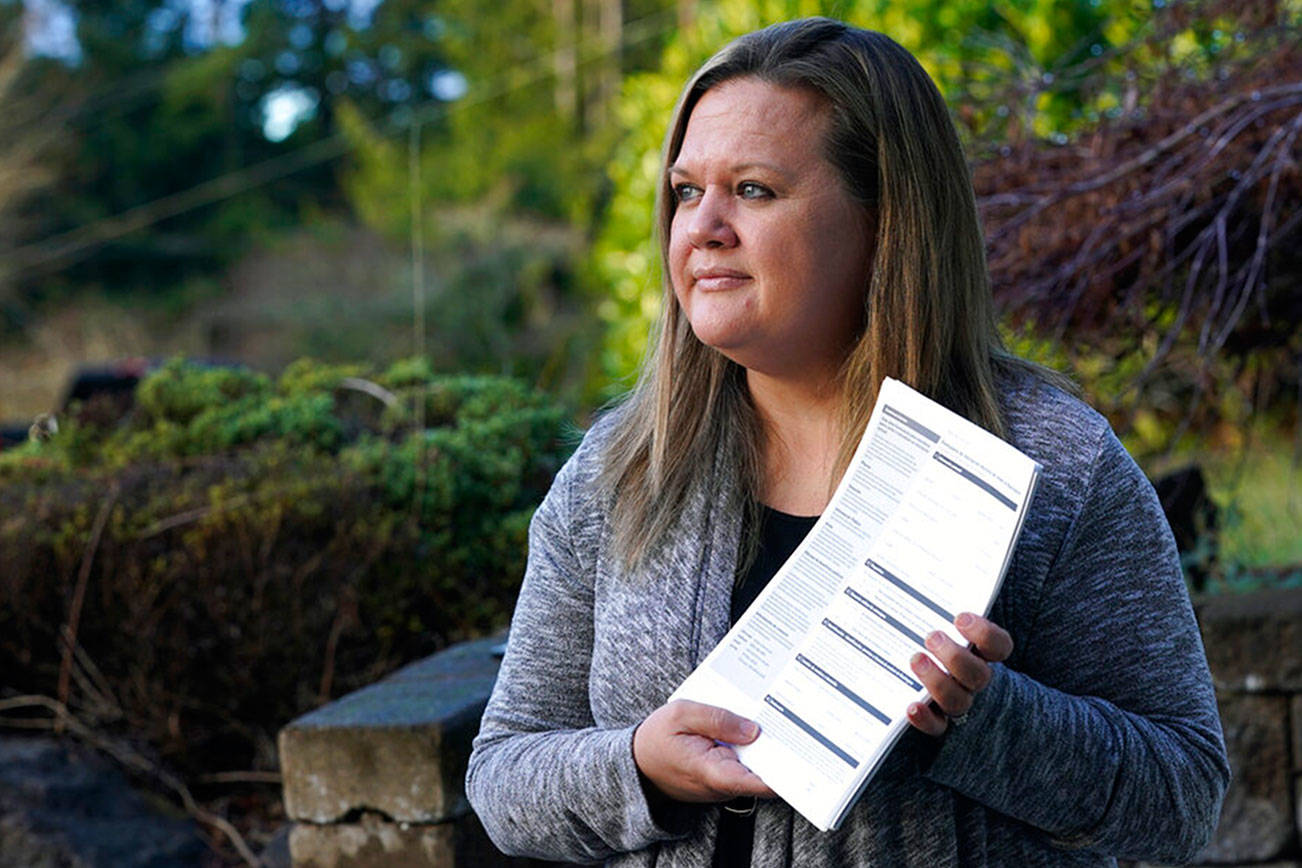 Rep. Tarra Simmons, D-Bremerton, holds blank voter registration forms as she poses for a photo Wednesday, Dec. 9, 2020, at her home in Bremerton, Wash. Simmons, believed to be the first formerly incarcerated person to win election to the Statehouse, is now working to help restore voting rights to people in Washington state who are out on parole or probation after serving prison time. (AP Photo/Ted S. Warren)