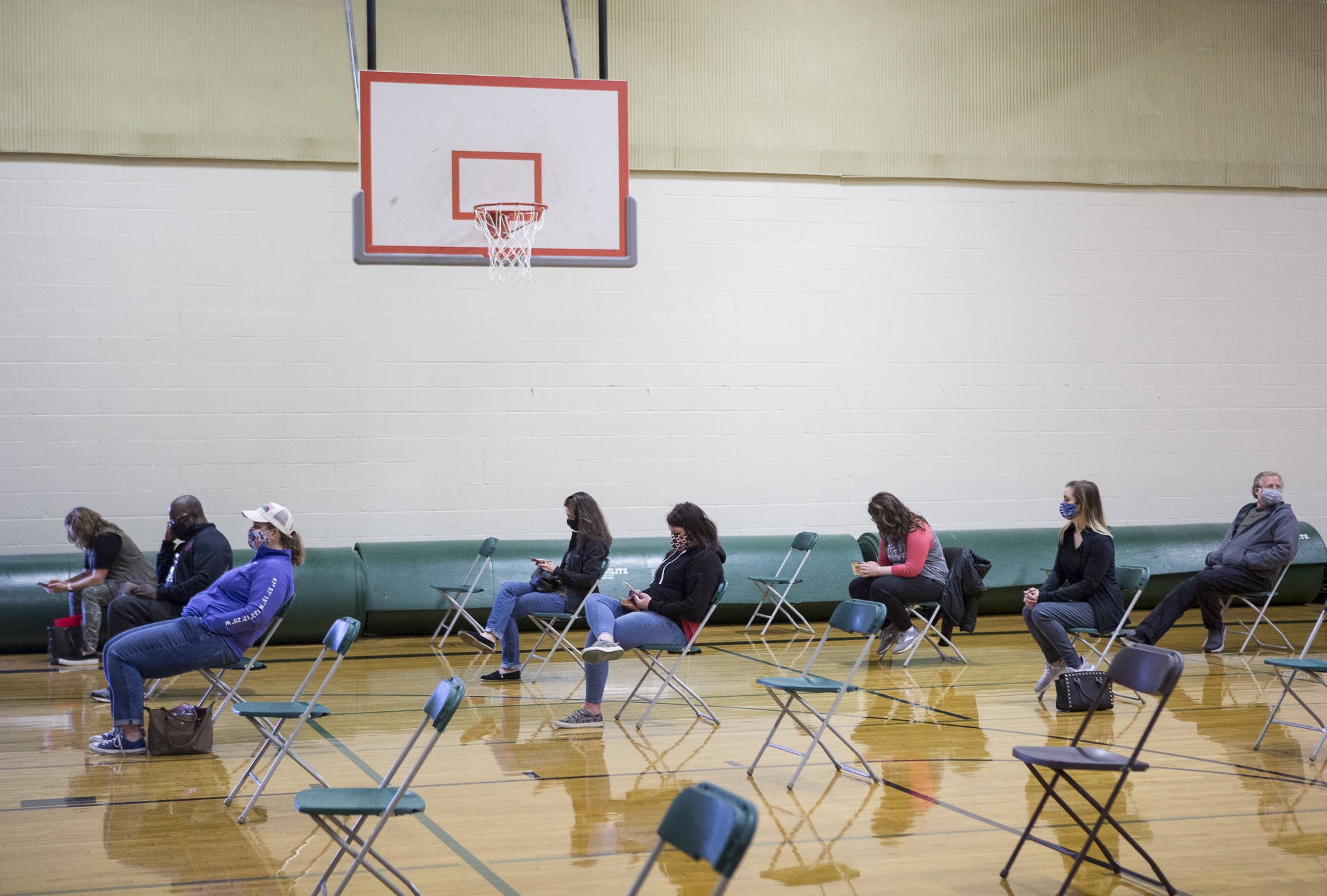 Everett School District teachers and staff wait in the Evergreen Middle School gym for 15 minutes after being vaccinated for COVID-19 on Saturday. (Olivia Vanni / The Herald)
