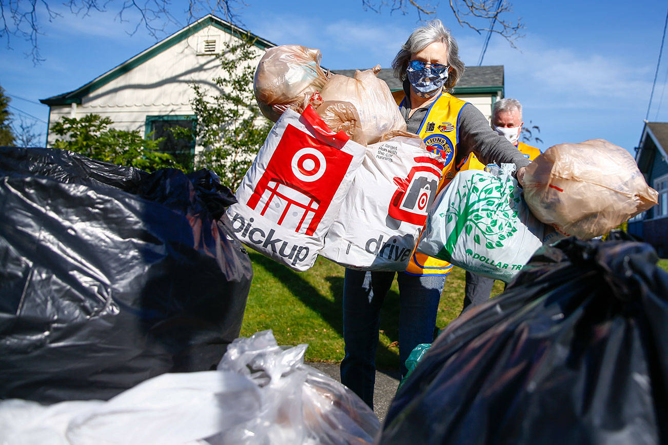 Renee Dierling adds plastic bags to the collection pile Friday afternoon in Snohomish on March 12, 2021. (Kevin Clark / The Herald)