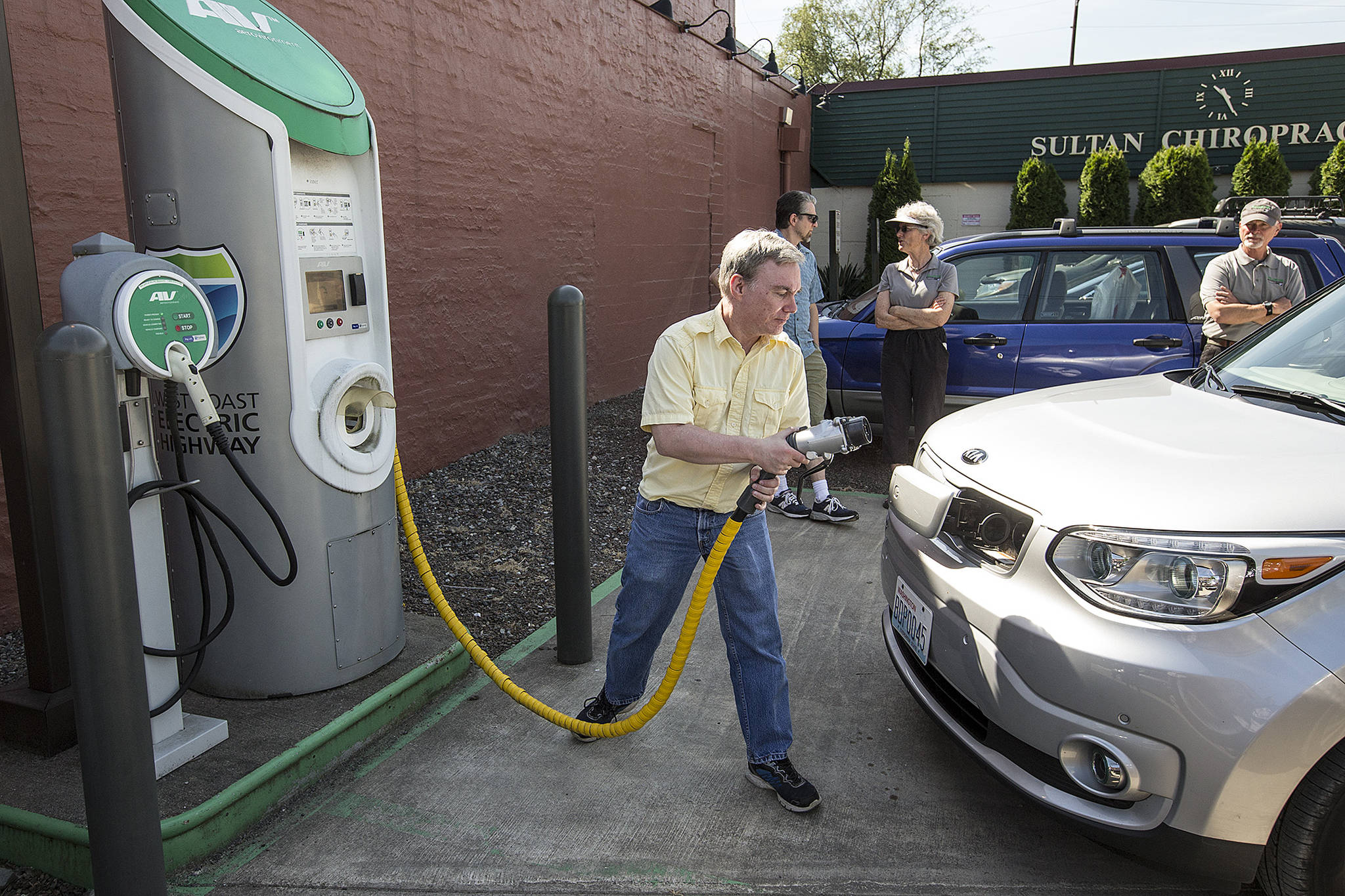 Brian Henderson, of Renton, plugs in his Kia Soul EV, an electric vehicle, June 7, 2017 at a charging station in Sultan during a trip from Everett's city hall to Spokane's city hall late to demonstrate the convenience of charging locations along U.S. 2. The Snohomish County PUD offers incentives for its customers who buy an EV and install a level 2 charging station at home. (Ian Terry / Herald file)
