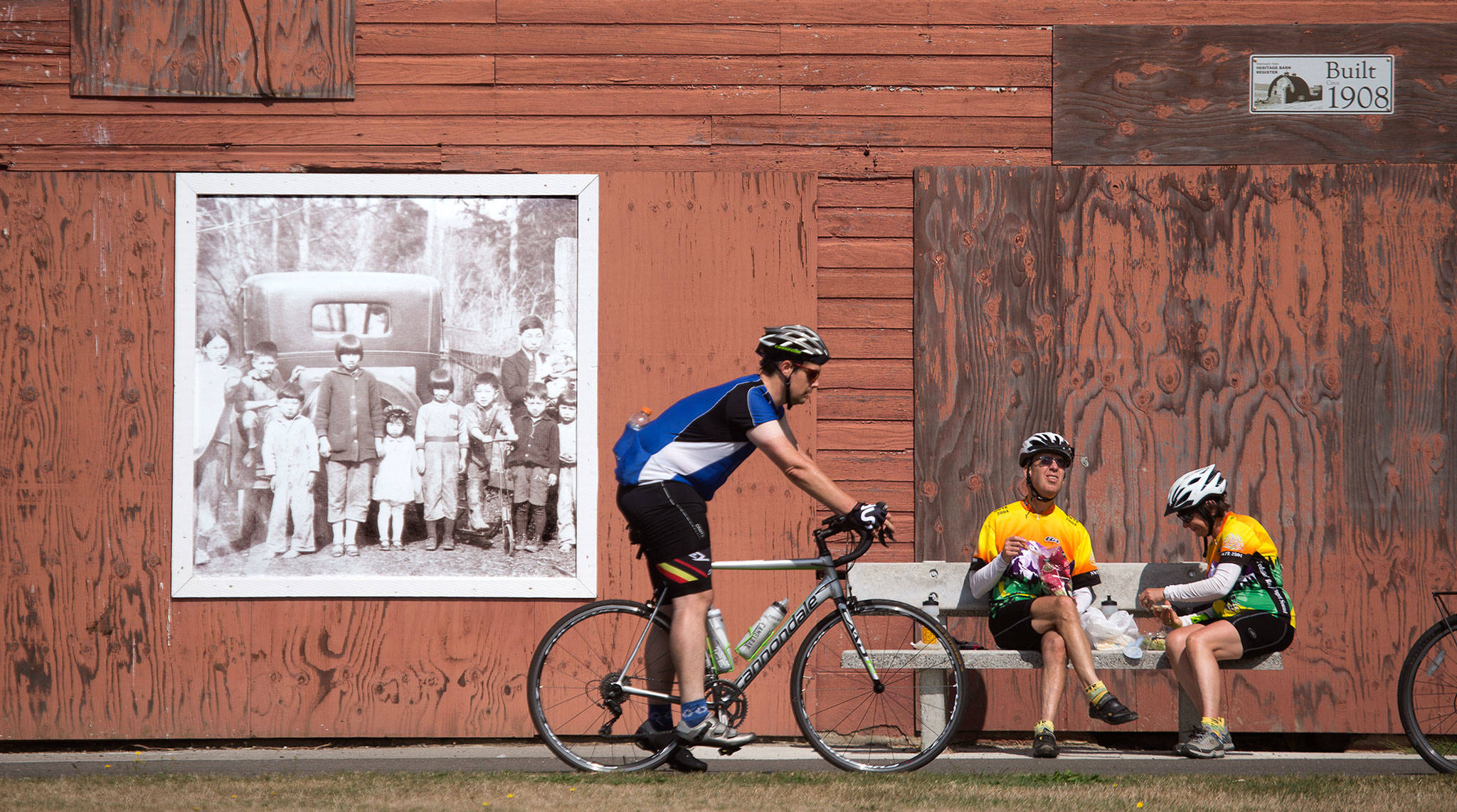 A portrait of the Nakashima family, who were sent to Japanese internment camps during World War II, fades in the sunlight as riders take a break at the Nakashima Barn at the north end of the Centennial Trail in Snohomish County on Sept. 2, 2019 in Arlington. (Andy Bronson / Herald file)