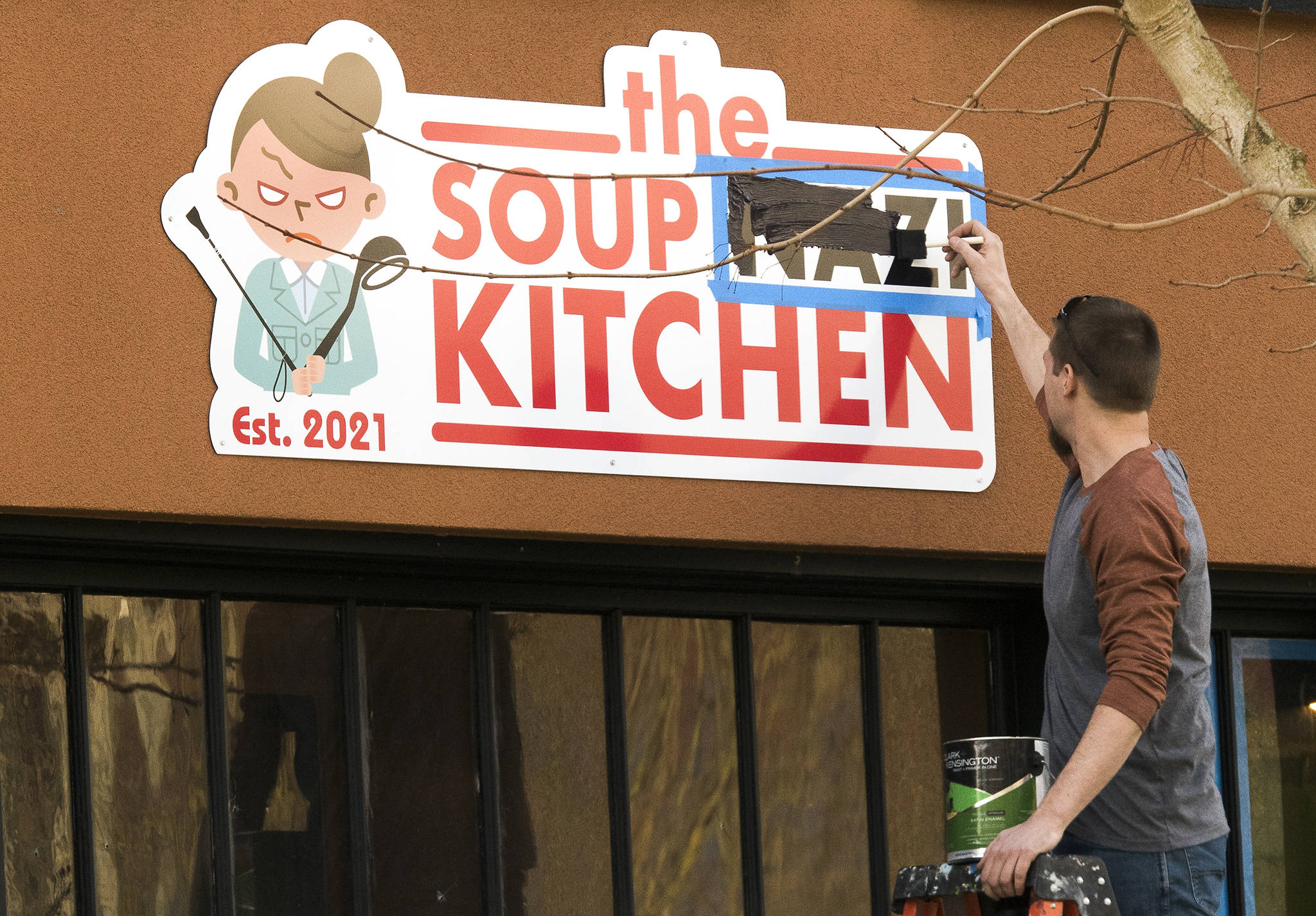 """A man paints over the word """"Nazi"""" at the Soup Nazi Kitchen on Hoyt Avenue on Wednesday in Everett. (Andy Bronson / The Herald)"""