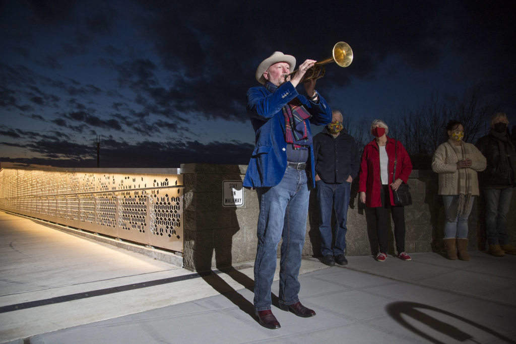 Kevin McKay, who for the past year has been playing Taps from his Everett deck every evening, marks the pandemic year by playing Taps on his horn from the Grand Avenue Park pedestrian bridge on Monday in Everett. (Andy Bronson / The Herald)