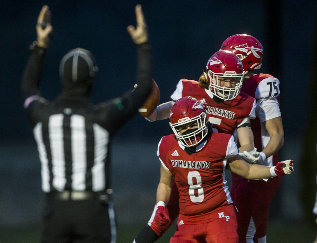 Marysville-Pilchuck's Kaden Mallang, left, and Kaleb Potts, right, celebrate Dylan Carson's touchdown during the game on Friday, March 19, 2021 in Marysville, Wa. (Olivia Vanni / The Herald)